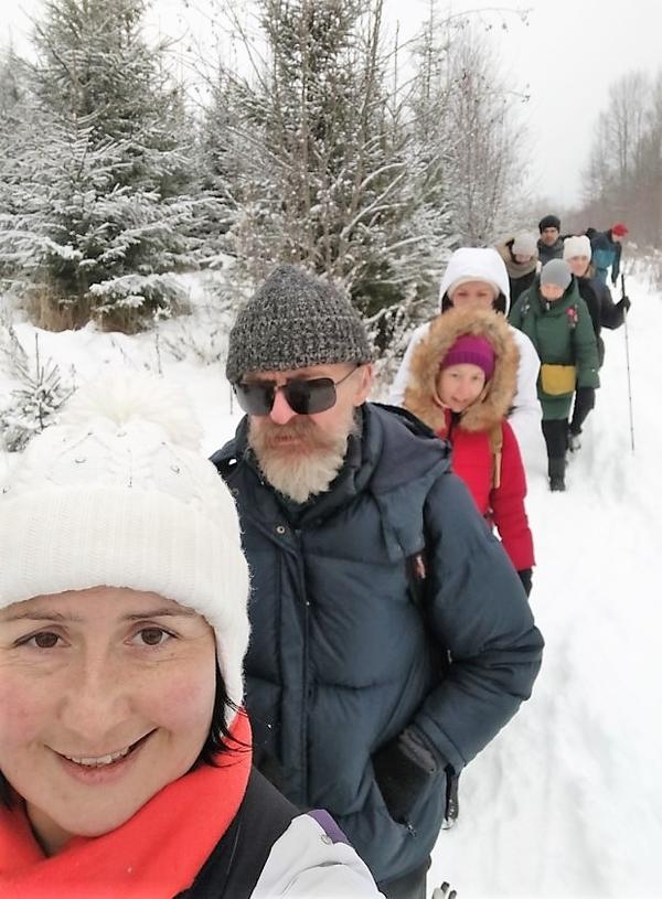 На фото: участники похода идут друг за другом по снежной тропинке