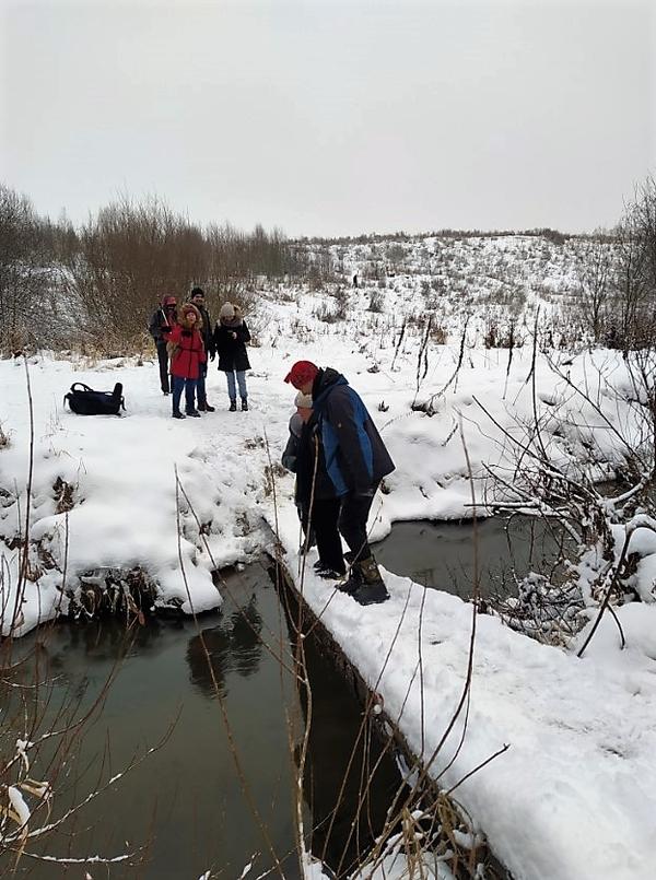 На фото: участники похода при помощи волонтеров переходят небольшой деревянный мостик через реку