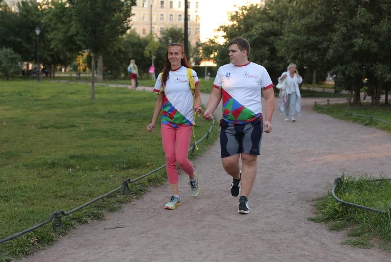 На фото: Владимир Васкевич в белой футболке, шортах и кроссовках бежит по дорожке парка рядом с девушкой в розовых штанах, белой футболке и с желтым рюкзаком за спиной. Владимир и девушка держатся руками за специальный ремешок