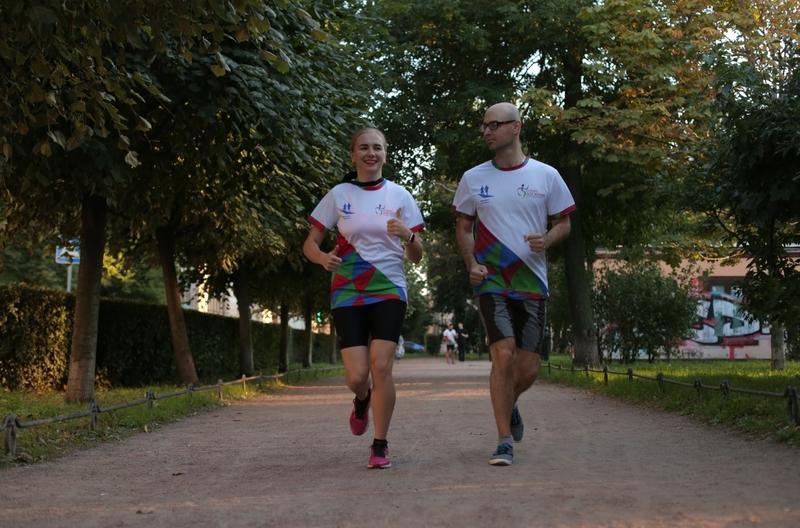 На фото: незрячий человек в шортах и футболке бежит по ровной дорожке в парке рядом с волонтером