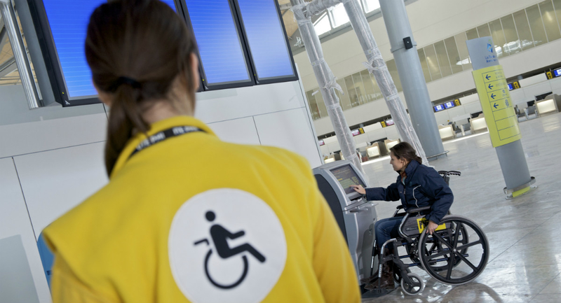 Image: airport employee and a woman in a wheelchair printong boarding pass